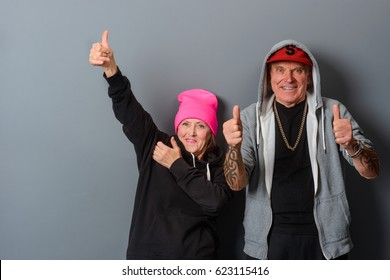 Horizontal photo of two elderly people in young style clothes making gestures with both hands over gray background. Cheerful grandparents at a party. Retirement is not boring.
