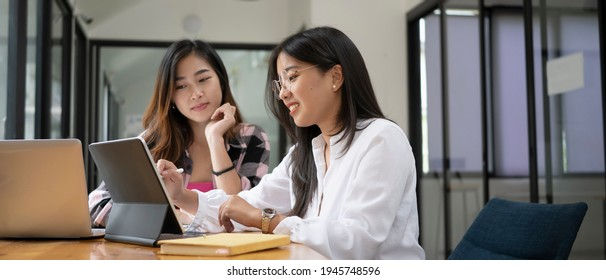 Horizontal photo of two female college student working on digital tablet and  talking about lessons comparing together.