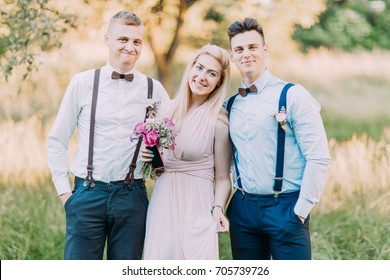 The horizontal photo of the two modern-dressed best men and the bridesmaid with the pink bouquet at the background of the sunny field.