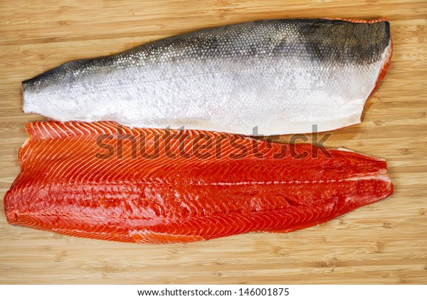 Horizontal photo of two Red Salmon fillets, one skin side up, on natural bamboo cutting board