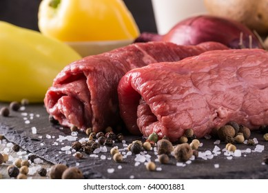 Horizontal photo of two rolled beef slices. Meat is prepared for roulade and placed on black slate stone with several spices and salt. Vegetable is too around in bowls.