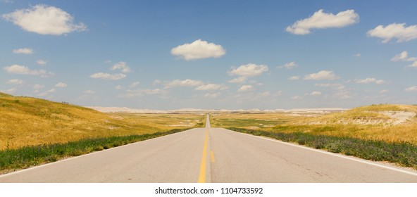 Horizontal Photo of an Ultra Wide North Dakota Highway with yellow lines, blue sky and clouds
