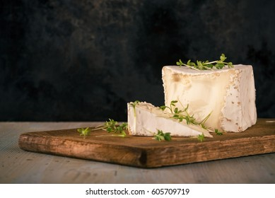 Horizontal photo with unusual camembert. Cheese with cube shape with arugula on vintage chopping board with cut off portion. Black worn baking tray is used as background.