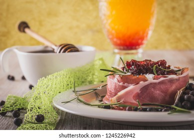Horizontal photo of whole camembert. Cheese is wrapped in dry ham and has cranberries on top. Cheese is on white plate with spilled juniper fruit around on wooden board with worn color.