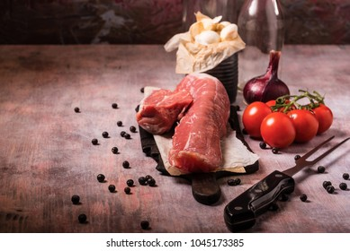 Horizontal photo of whole pork tenderloin. Raw meat is on vintage wooden board with big fork, white garlic in old can and few red cherry tomatoes. Two empty bottles are in background.
