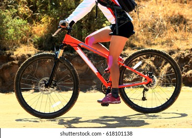 Horizontal photo of a woman riding her orange mountain bike with kinesiology tape on her knees during a race