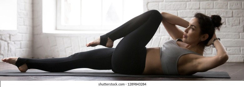 Horizontal photo woman wearing black panties grey bra lying on mat doing bicycle crunches criss cross fitness exercise at sport center or home banner for website header design with copy space for text