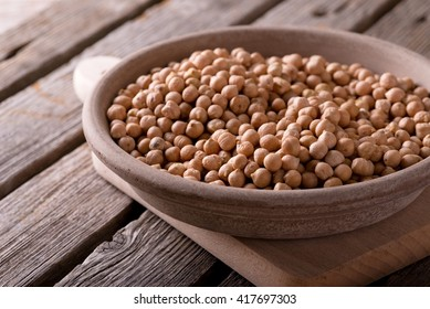 Horizontal photo. Yellow dry chickpeas. Chickpeas in clay bowl. Earthen plate with legumes. Bowl on chopping board. Bowl on old wooden board. Old worn wooden board with grey color.