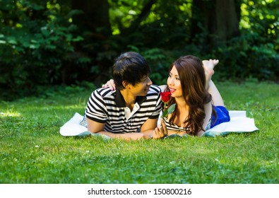 Horizontal photo of young adult couple, lying on blanket, while looking at each other with sharing a single red rose with green grass and trees in background
