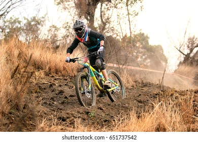 Horizontal photo of a young enduro mountain biker riding amazingly fast downhill in a dusty trail