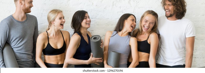 Horizontal photo young laughing people wearing activewear girls guys standing in row near wall laughing joking talking resting after workout healthy lifestyle concept, banner for website header design