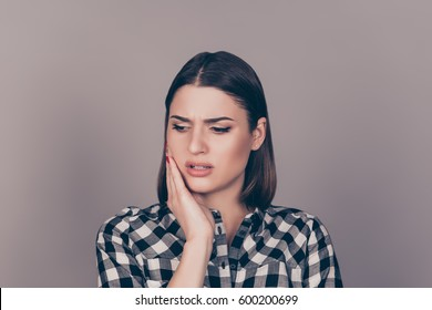 A horizontal photo of a young worried woman in checkered shirt suffering from strong toothache and touching her cheek