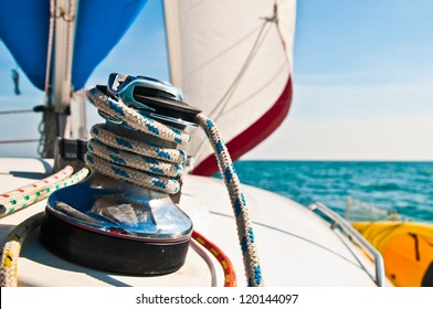 Horizontal photograph of a blue and white line wrapped around a large metal cleat with sail set in background.