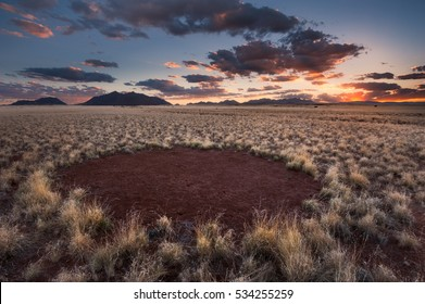 A horizontal photograph of a fairy circle taken during sunset with orange clouds in the Namib Naukluft Park