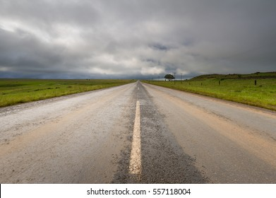 A horizontal photograph on a tar road with a dramatic stormy sky above during the afternoon in Dullstroom