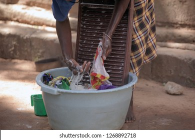 horizontal photography of an african girl washing laundry on a washboard, outdoors on a sunny day in the Gambia, Africa