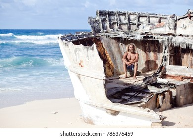 Horizontal picture. Alone sad curly-berded man is sitting on the wreck of the ship on the white sand beach. Blue ocean on the background. Robinson Crusoe