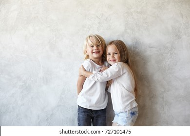 Horizontal picture of cute European little couple cuddling indoors: smiling beautiful girl hugging blonde handsome boy who feeling shy. Male and female kids wearing similar clothes, playing together