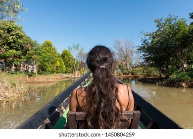 Horizontal picture of long hair, brunette woman looking the beautiful nature during boat trip in Inle Lake, Myanmar