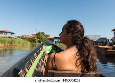 Horizontal picture of long hair, brunette woman during boat trip in a sunny day in Inle Lake, Myanmar