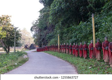Horizontal picture of many aligned monks statues at the road to Kaw Ka Thaung Cave, located close to Hpa-An, Myanmar