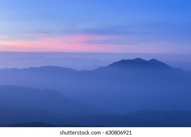 horizontal picture of top blue mountain with mist and twilight blue and red sky