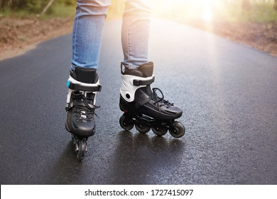 Horizontal picture of unknown person rollerskating, rollerskates being on wet road, having sun on background, black modern rollerskates used in everyday life, leisure activities. Movement concept.