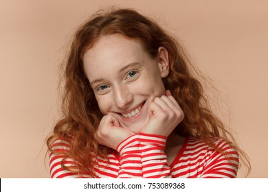 Horizontal picture of young attractive redhead European lady isolated on peach background, her head resting on fists, smiling warmly and friendly while listening to her mate with care and attention