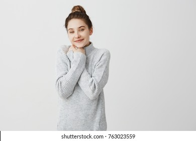 Horizontal portrait of adorable woman tied her hair in topknot smiling being positive. Beautiful female hairdresser having break putting hands on chest in joy. Leisure, person concept