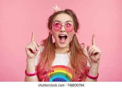 Horizontal portrait of astonished fashionable good looking female model looks with widely opened mouth up, sees something strange or unexpected, indicates with fore fingers, stands against pink wall