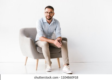 Horizontal portrait of attractive caucasian guy wearing stylish formal clothing sitting in armchair and looking at camera isolated over white background