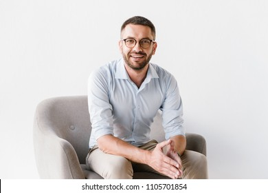 Horizontal portrait of attractive caucasian guy wearing stylish formal clothing sitting in armchair and looking ahead with smile isolated over white background
