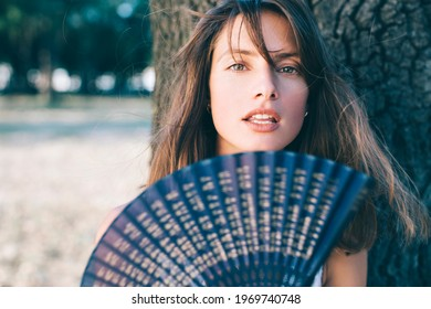 Horizontal portrait of a beautiful brunette young woman with blue hand fan.