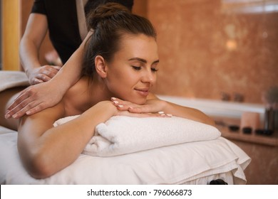 Horizontal portrait of a beautiful happy young woman smiling joyfully lying at the spa center receiving back massage by a professional masseur copyspace hotel resort recreation leisure