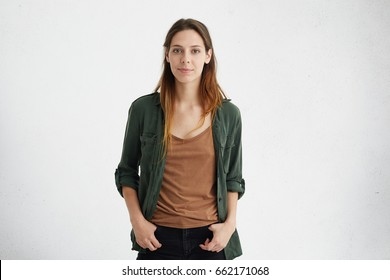 Horizontal portrait of beautiful woman with European appearane having oval face, dark attractive eyes and long straight hair dressed casually feeling relaxed while standing with hands in pockets