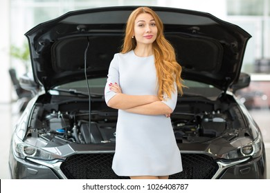 Horizontal portrait of a beautiful young happy woman smiling with her arms folded posing in front of an automobile with an open hood at the dealership salon repairing machinery engine motor horsepower