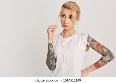 Horizontal portrait of blond, european girl with pierced nose, blue eyes, tattoo on arms, dressed in casual white t-shirt, listen music via headphones  and looking aside. Copyspace. Isolated