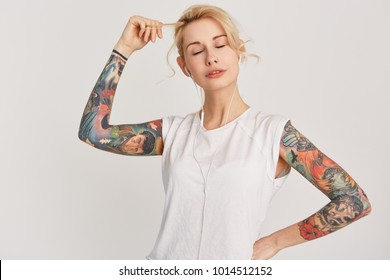 Horizontal portrait of blond, european girl with pierced nose, closed eyes, tattoo on arms, dressed in casual white t-shirt, listen and enjoy music with earphones. Isolated on white wall