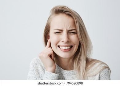 Horizontal portrait of blonde caucasian female dressed casually has headache after noisy party, clenches teeth and holds hand behind her ear. Irritated young female expressing negative emotions.