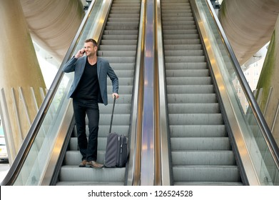 Horizontal portrait of a business man talking on the phone while going down escalator