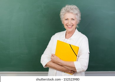 Horizontal portrait of a Caucasian cheerful female senior teacher holding a yellow file with a blank chalkboard behind