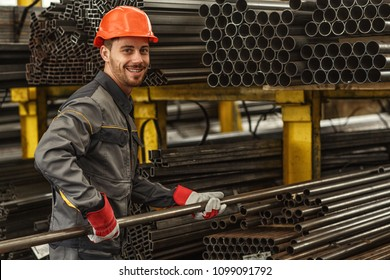 Horizontal portrait of a cheerful industrial worker in protective uniform and hardhat smiling to the camera over his shoulder while stacking steel pipes at the storage of a metalworking company
