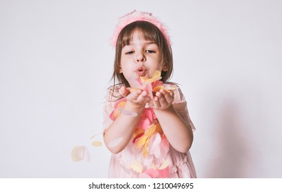Horizontal portrait of cute little girl wearing pink dress in tulle with princess crown on head isolated on white background blowing confetti. Pretty girl with confetti in hands for birthday party