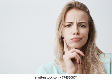 Horizontal portrait of displeased woman with blonde hair has indignant expression of face, frowns eyebrows, can`t understand something. Attractive puzzled dissatisfied female keeps hand on chin