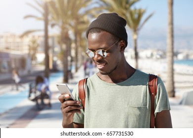 Horizontal portrait of fashionable black African male in summer shades and black hat travelling in big city holding smartphone using online maps trying to find right route. Recreation and lifestyle