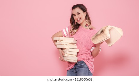 Horizontal portrait of a girl with a stack of books, on a pink background, lifestyle and education concept