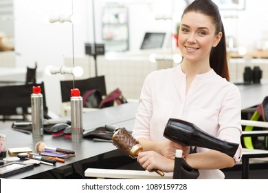 Horizontal portrait of a gorgeous cheerful young female professional hairdresser holding blowdryer smiling to the camera posing at her beauty studio. Occupatiob, job, beauty industry concept