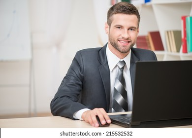 Horizontal portrait of handsome businessman sitting at the table working with laptop looking at the camera and happy smiling in office background