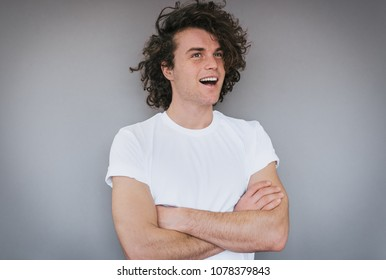 Horizontal portrait of handsome happy young male with curly hair, wearing white t-shirt, looking away posing against grey background. Copy space for advertisement. People and emotion concept.