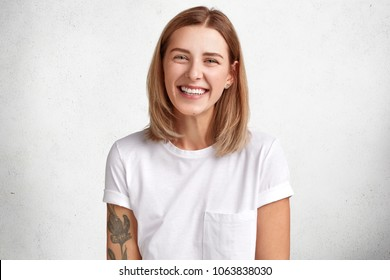 Horizontal portrait of happy female has cheerful expression, dressed in white casual t shirt, expresses positiveness, being glad to spend free time with boyfriend. Smiling woman with stylish hairdo
